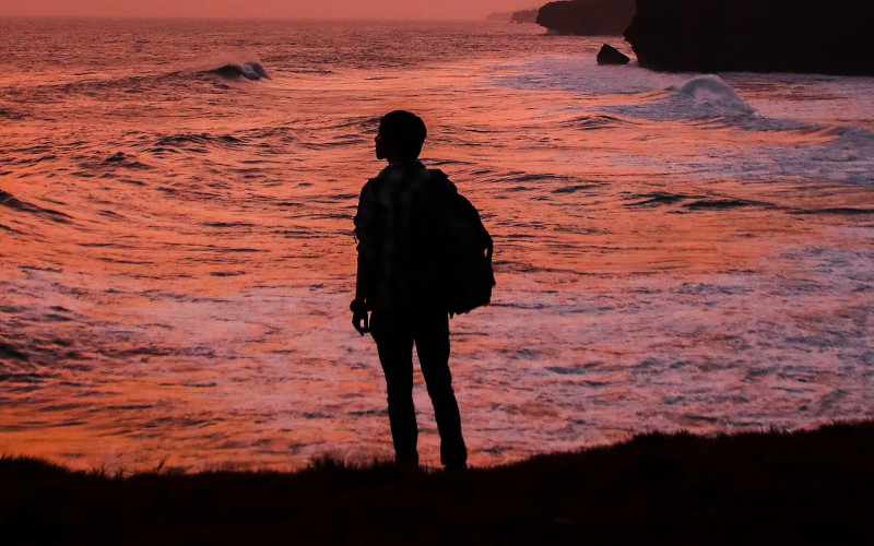 Man With Backpack On Seashore